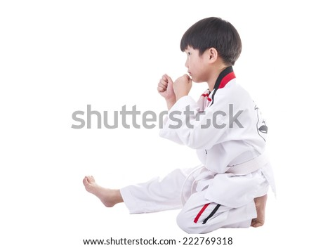 Little boy in taekwondo suit on a white background.