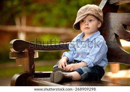 little boy in the blue shirt and brown cap is sitting on the wooden bench in the park - stock photo