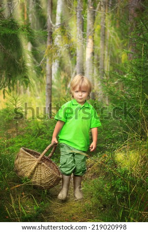Little boy in the forest walking with straw basket of mushrooms - stock photo