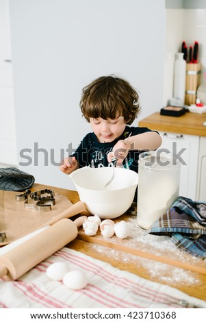 Little boy in the kitchen helping to cook the dough for baking