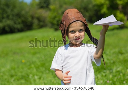Little boy in the old helmet pilot playing with paper airplanes. - stock photo