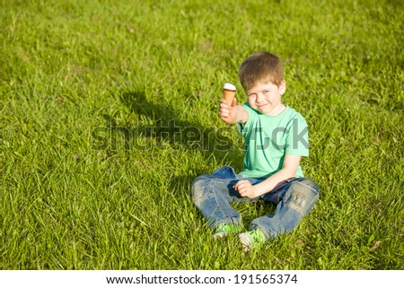 little boy in the park on the green grass eating ice cream - stock photo