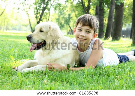 Little boy in the park with a golden retriever dog