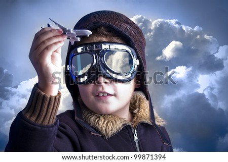 Little boy in the pilot`s hat. Boy as an old style pilot holding a toy airplane - stock photo