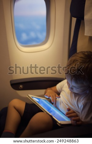 Little boy in the plane sitting by the illuminator and using touch pad to entertain himself