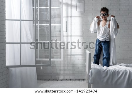 Little boy in the role of the pilot parachute with a sheet on a bed - stock photo