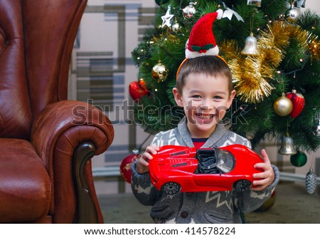 Little boy in the santa's red hat seating near the christmas tree with cool red car. He is smiling and having fun. Perfect for christmas illustrations.   - stock photo