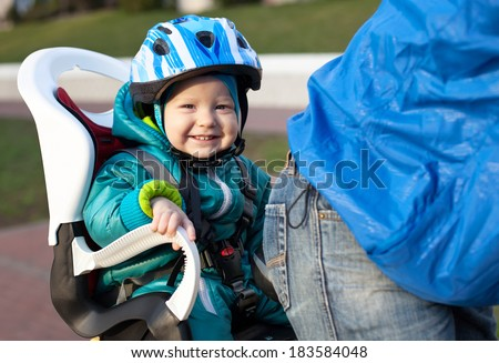 Little boy in the seat bicycle behind father - stock photo