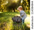 little boy in the suite with big bag in the park - stock photo