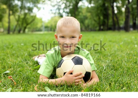 Little boy in the summer park with a ball