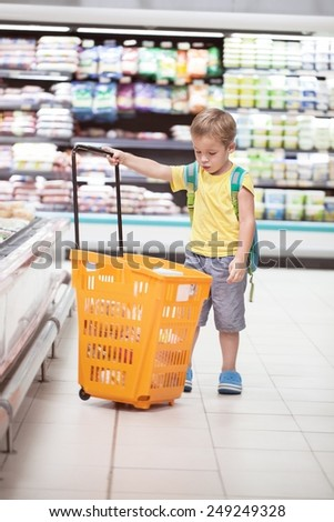 Little boy in the supermarket looking at big full  shopping cart. Child going shopping alone - stock photo
