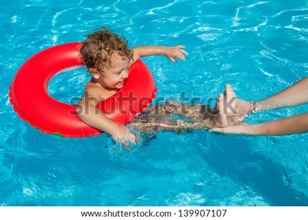 little boy in the swimming pool  with rubber ring