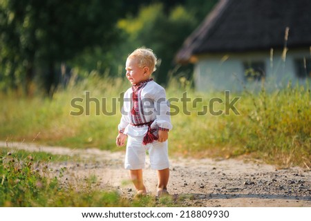 little boy in the Ukrainian embroidered shirt crying alone on the road