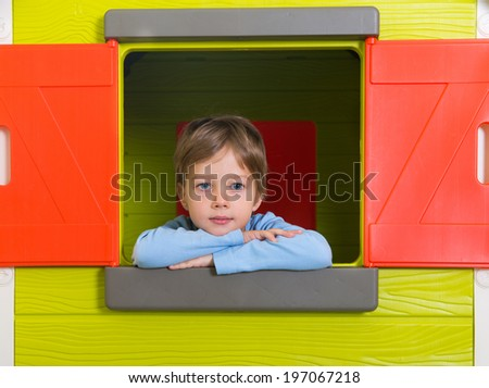 Little boy in toy house window in kindergarten - stock photo