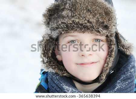 little boy in winter a fur hat in winter - snow on the scarf and hat - stock photo