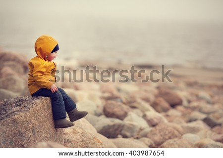 Little boy in yellow raincoat is sitting on rocky shore of Finnish Gulf and looking at the sea. Image with selective focus and toning - stock photo