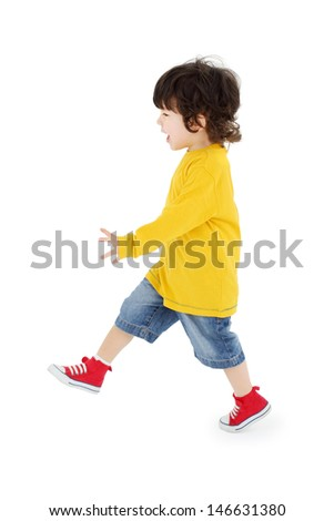 Little boy in yellow shirt walks isolated on white background. - stock photo