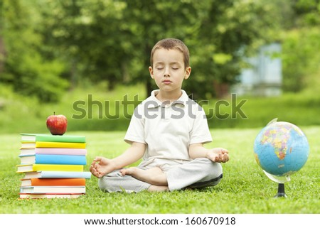 Little boy in zen meditation preparing to be good student - stock photo