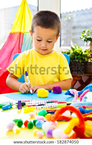 Little boy indoors painting and gluing - stock photo