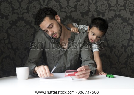 Little boy is climbing on his dad, playing with his toy car. His dad is trying to make bill payments through the phone. - stock photo