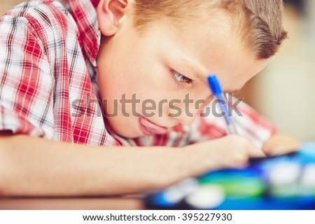 Little boy is doing his homework for elementary school. - stock photo
