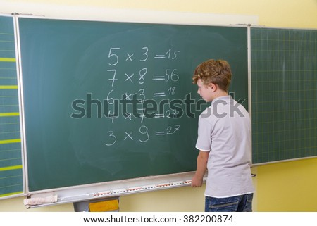 Little boy is doing some maths at a blackboard in school - stock photo