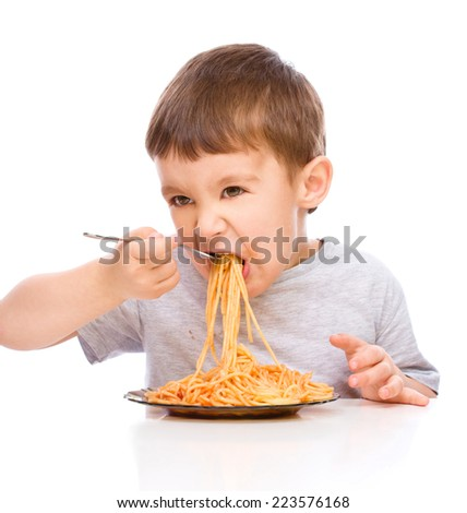 Little boy is eating spaghetti using fork, isolated over white - stock photo