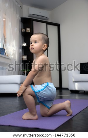 Little boy is engaged in gymnastics on a yoga Mat, standing on one knee, age 2 years - stock photo