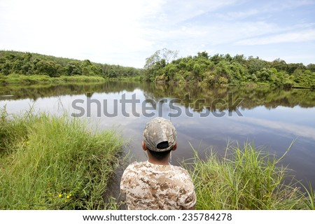 Little boy is fishing at  on the lake  - stock photo