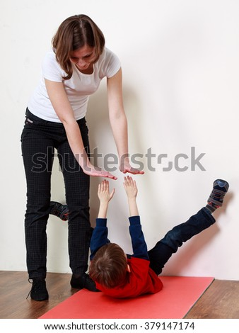 Little boy is going an exercise on a mat with the help of a trainer - stock photo