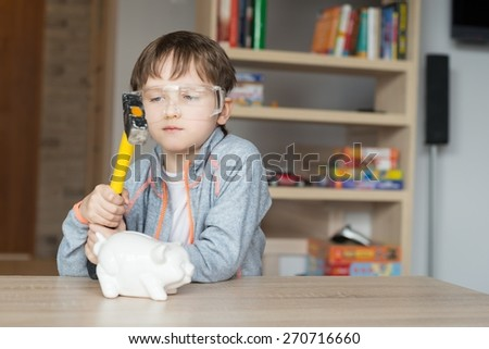 Little boy is going to break his piggy bank - proctective glasses on his eyes - stock photo