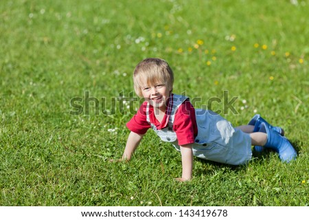 Little boy is having fun on the grass in the park - stock photo