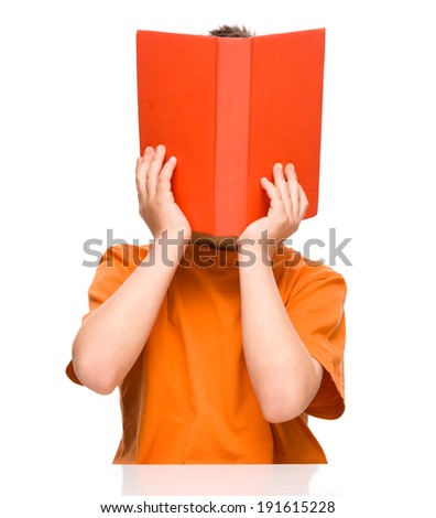 Little boy is hiding behind a book while sitting at table, isolated over white - stock photo
