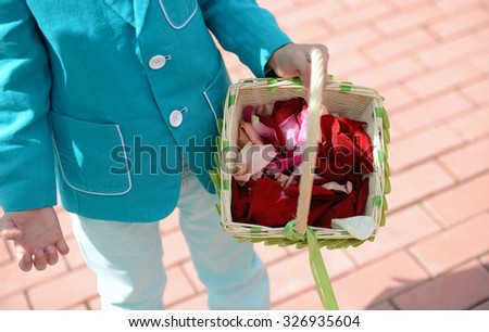 Little boy is holding a basket of rose petals. Beautiful wedding colorful bouquet for bride. Beauty of colored flowers. Close-up bunch of florets. Bridal accessories. Details for marriage - stock photo