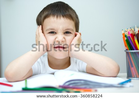Little boy is holding bunch of color pencils - stock photo