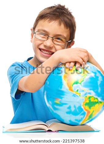 Little boy is holding globe while sitting at table, isolated over white - stock photo