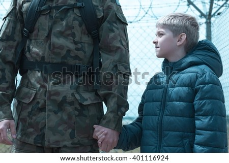 Little boy is holding his father soldier hand  - stock photo