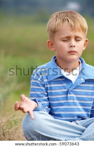little boy is meditating in the lotus position on a background of green meadows