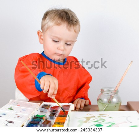 Little boy is painting by aquarelle on a paper on a grey background