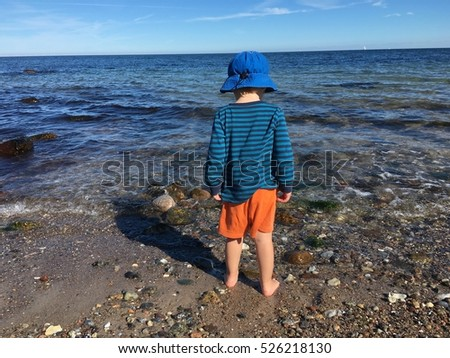 Little boy is playing barefoot on the beach