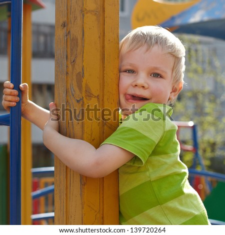 Little boy is playing on playground - stock photo