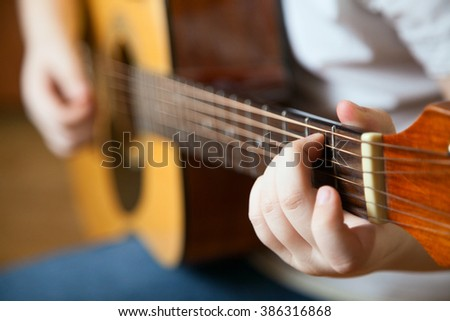 Little boy is playing the guitar - stock photo