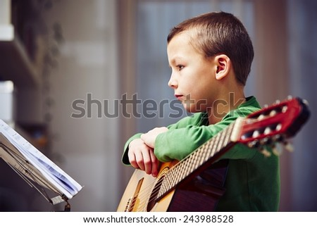 Little boy is playing the guitar at home - stock photo