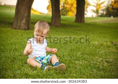 little boy is playing while sitting on the lawn in the park