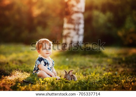 little boy is playing with a rabbit in the park. Concept love of animals and people, childhood.