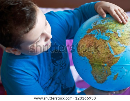 Little boy is playing with globe - stock photo