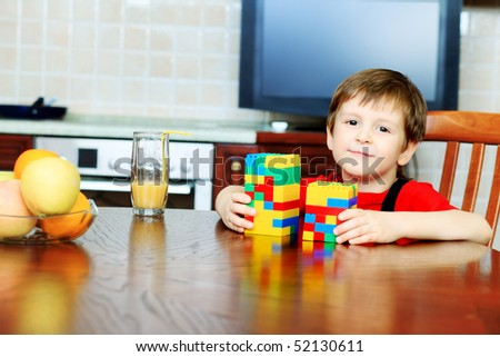 Little boy is playing with his toys at home. - stock photo