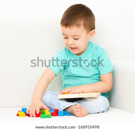 Little boy is playing with puzzle - stock photo