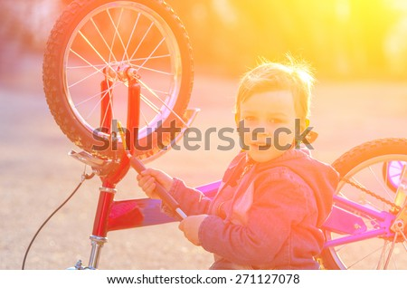 Little boy is pumped European wheel of his bike, sitting on the pavement and smiling against a bright setting sun. natural composition - stock photo
