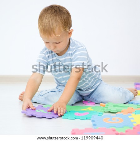 Little boy is putting together a big puzzle while sitting on the floor - stock photo